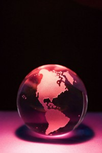 Glass globe on reddish pink background.